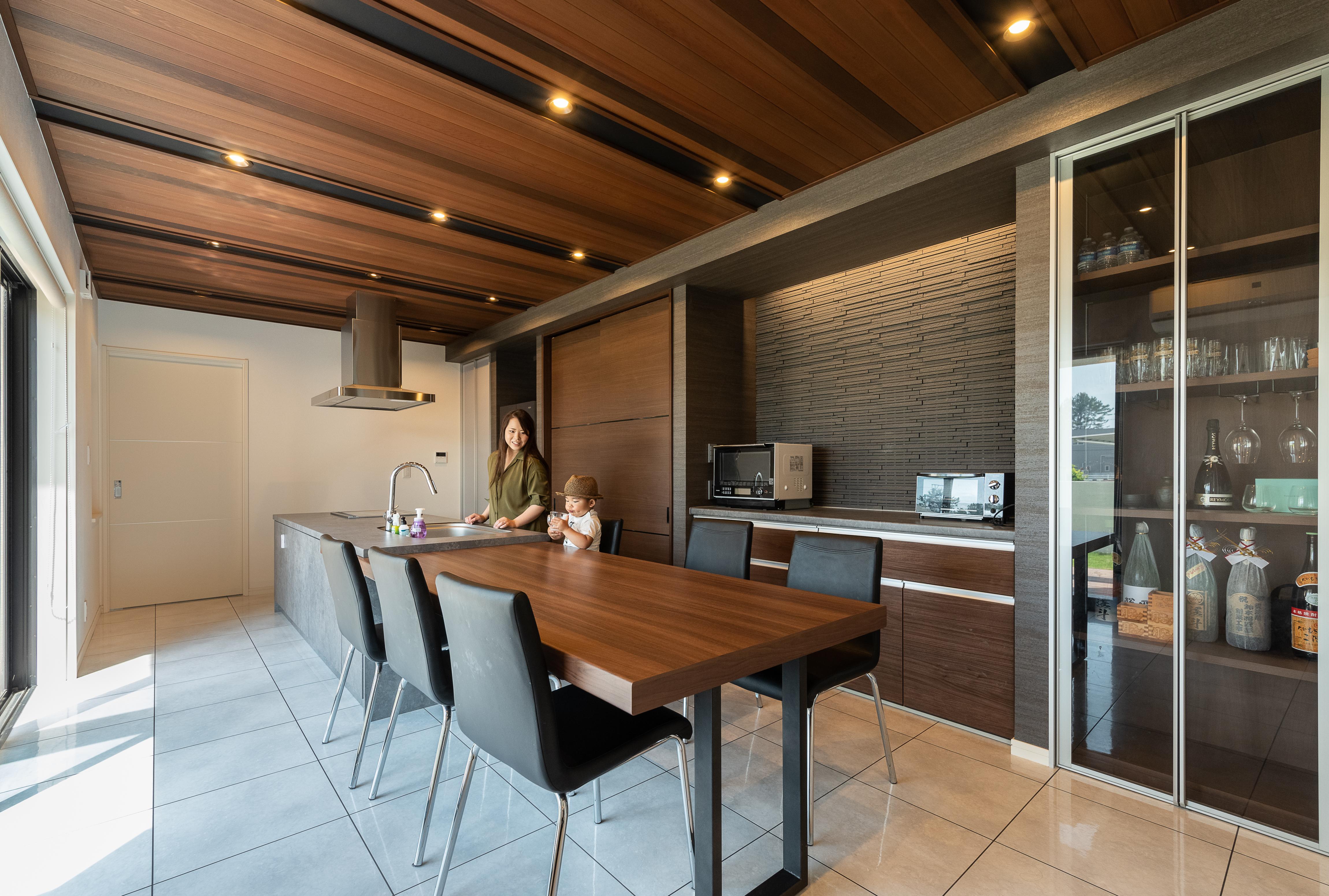 タイル張りの床と板張りの天井、テーブルの色や背面のタイル。素材と色のハーモニー。