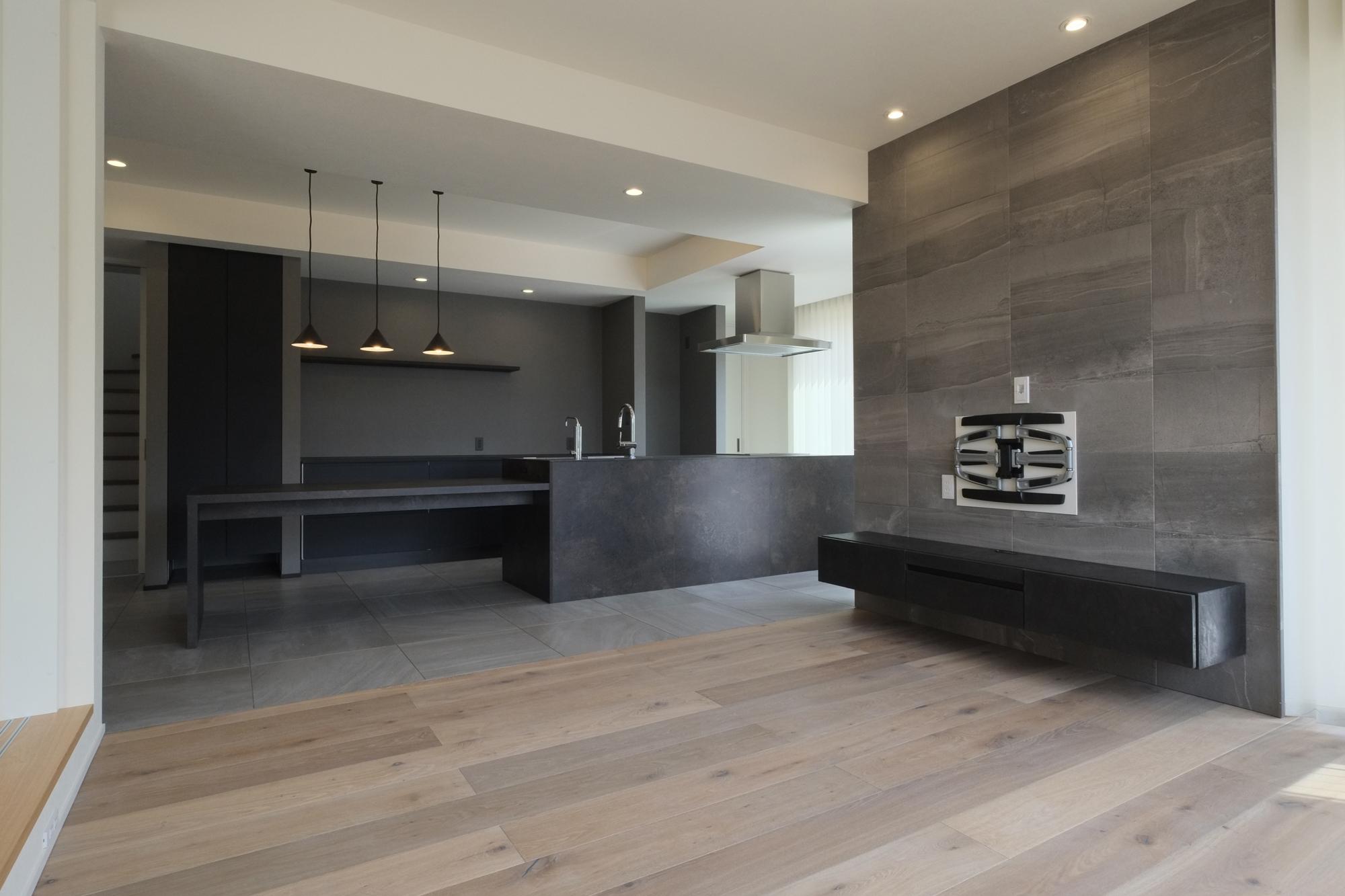 床の無垢材、タイルが貼られたアクセントウォール、キッチン。素敵なグレーグラデーション。