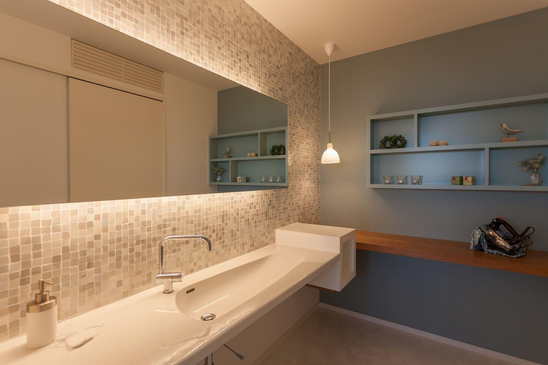 高級感のある美しいガラスタイルを貼った洗面室。アイロンがけスペースもございます。